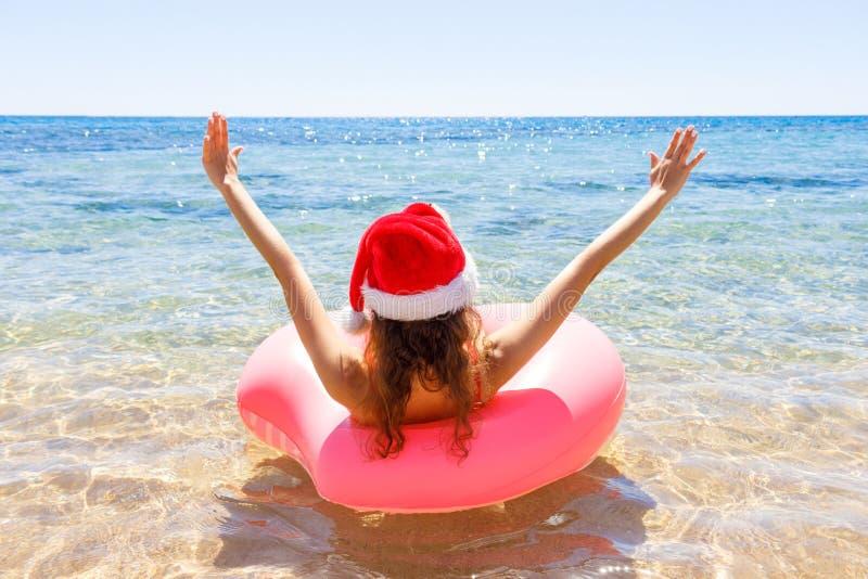 Galen simning med den uppblåsbara munken och julhatten på stranden i solig dag för sommar royaltyfri foto