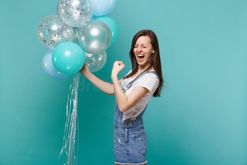 Galen skrikig ung flicka med stängda ögon som griper hårt om näven som vinnaren som firar rymma färgrika luftballonger arkivfoto