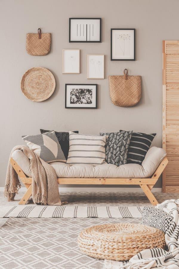 Galería de carteles blancos y negros y de accesorios de mimbre en la pared beige de la sala de estar escandinava imagenes de archivo