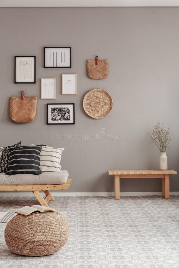 Galer?a de carteles blancos y negros y de accesorios de mimbre en la pared beige de la sala de estar escandinava imagen de archivo libre de regalías