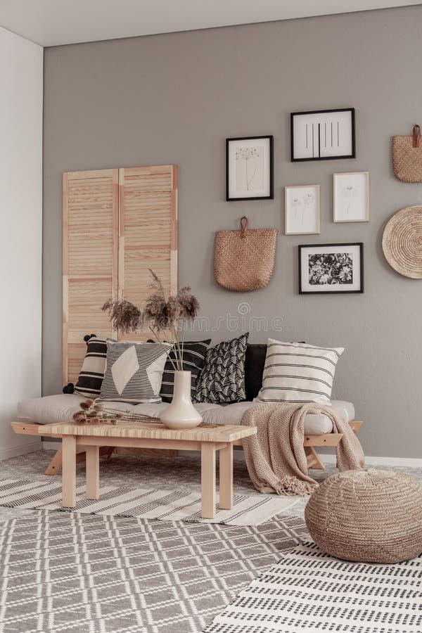 Galer?a de carteles blancos y negros y de accesorios de mimbre en la pared beige de la sala de estar escandinava fotografía de archivo