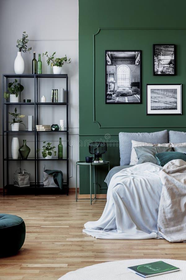 Galer?a del cartel blanco y negro en la pared verde detr?s de la cama gigante con las almohadas y la manta imagen de archivo libre de regalías