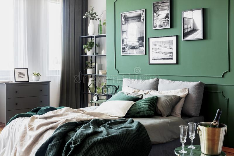 Galer?a del cartel blanco y negro en la pared verde detr?s de la cama gigante con las almohadas y la manta fotografía de archivo