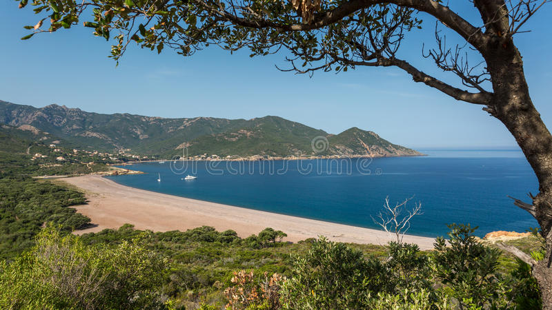 Galeria beach in Corsica. Galeria beach on the west coast of Corsica with boats moored in the blue Mediterranean sea stock photo