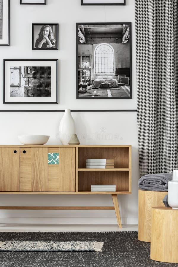 Galerie über hölzernem Schrank in der hellen Wohnung, die mit grauem Teppich Innen ist und drapiert Reales Foto stockfotografie