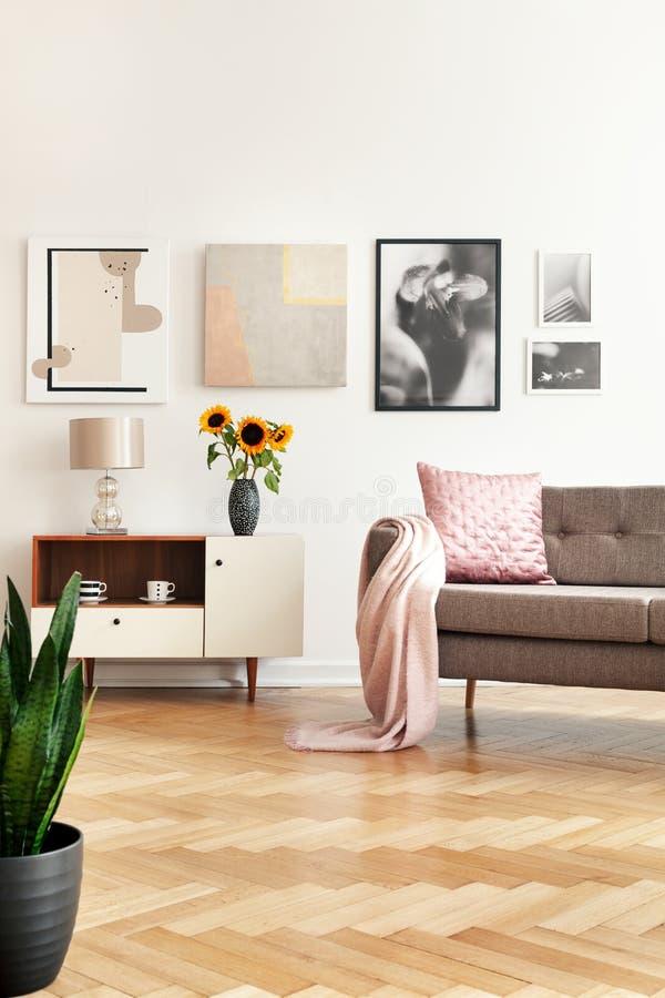 Galerie im weißen Wohnzimmerinnenraum mit Sofa mit rosa Kissen und Bettdecke, Sonnenblumen auf Schrank und Fischgrätenmusterboden stockfoto