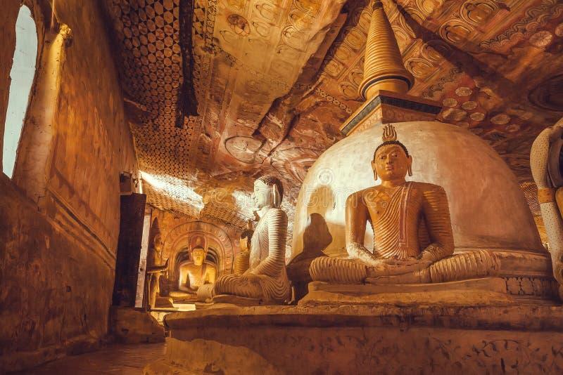 Galerij van het zitten in de standbeelden van meditatieboedha in oude holtempel met verfraaide muren en fresko stock afbeeldingen