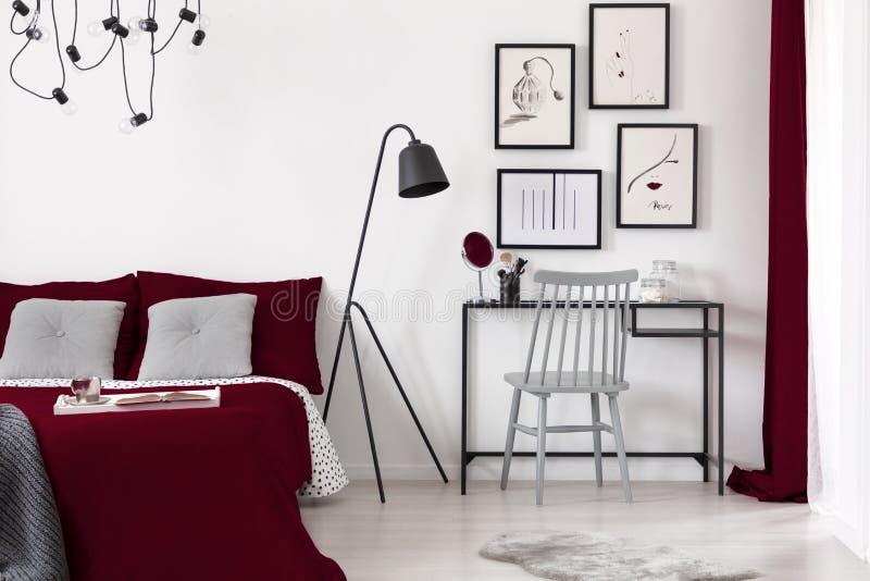 Galerij van illustraties op een witte muur boven een klein bureau dat naast een zwarte metaallamp en een bed van Bourgondië in mo stock afbeelding