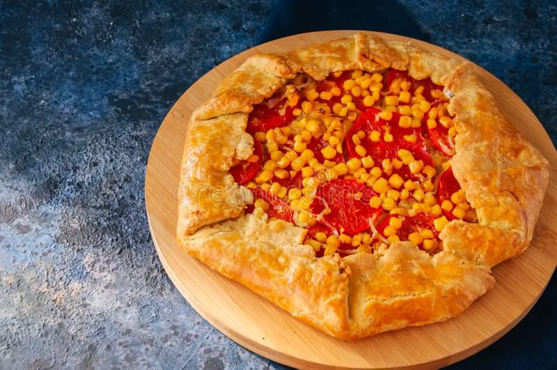 Galette do tomate e do milho doce em uma placa de madeira Vista superior azul imagem de stock royalty free