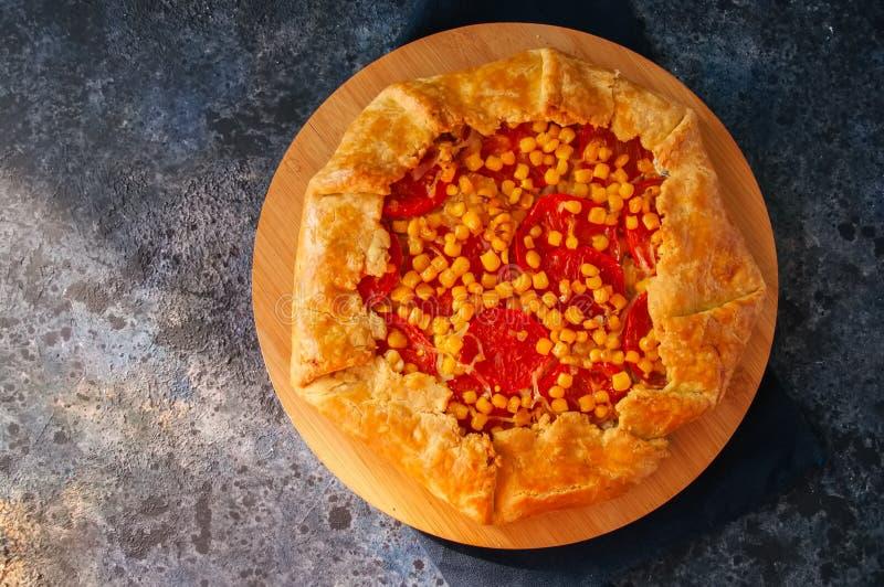 Galette do tomate e do milho doce em uma placa de madeira Vista superior azul foto de stock