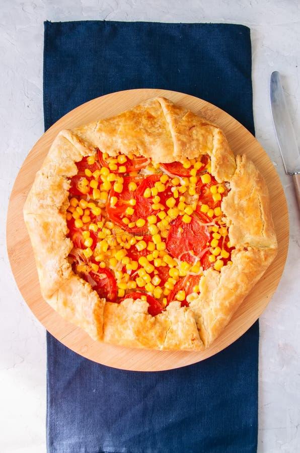 Galette do tomate e do milho doce em uma placa de madeira Vista superior branco imagem de stock