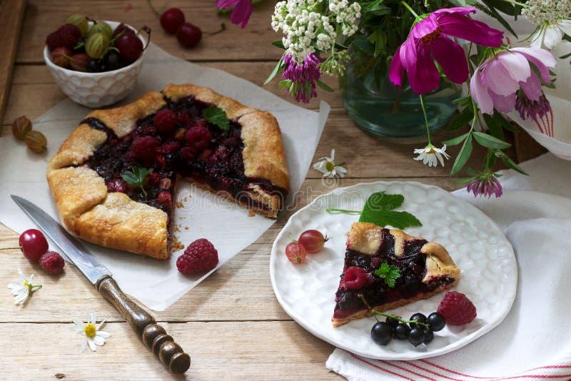 Galette dolce della torta con il materiale da otturazione succoso della bacca, le bacche ed i fiori selvaggi su un fondo di legno fotografie stock libere da diritti