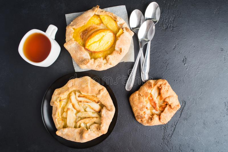 Galette vegetariano di cottura di tre dolci con una tazza di tè su fondo scuro, disposizione piana fotografie stock libere da diritti