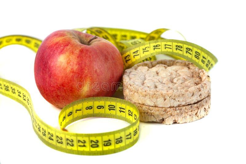 Galettes soffiati sani del cereale e mela rossa con nastro adesivo di misurazione fotografie stock libere da diritti