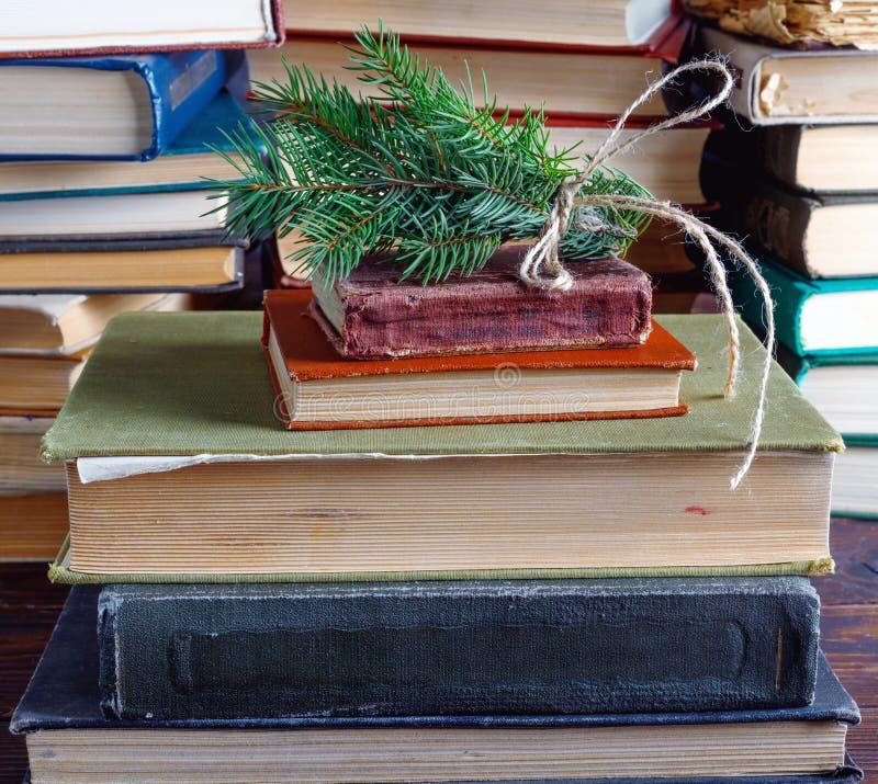 Galho do abeto vermelho amarrado acima com corda velha na pilha de livros velhos do vintage fotografia de stock