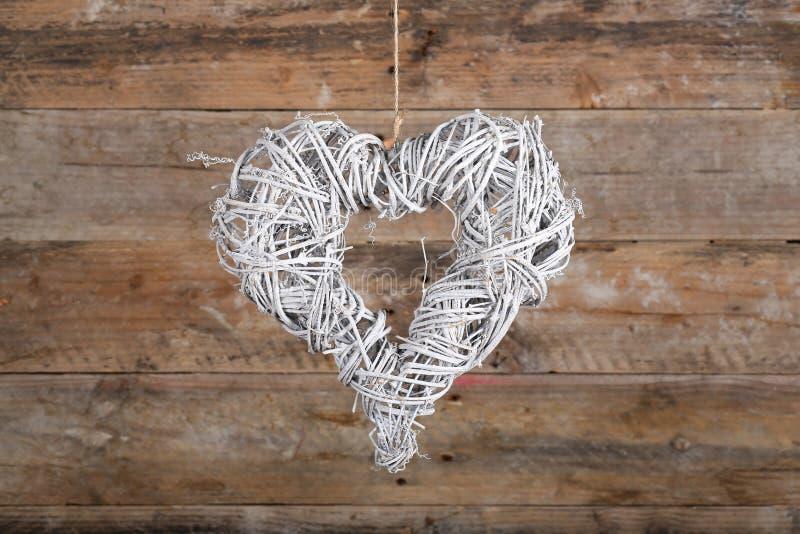 Galhos brancos da grinalda do Natal da forma do coração em Backgroun rústico velho imagens de stock