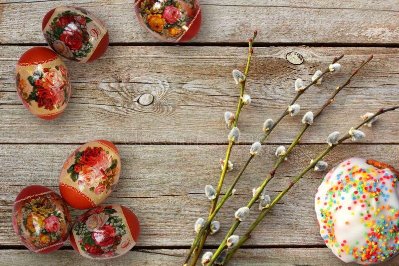 Galhos dos ovos da páscoa, do bolo e do salgueiro na tabela de madeira imagem de stock
