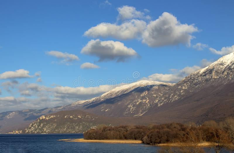 Winter landscape in Macedonia. Ohrid Lake and the picturesque hills of Galichitsa mountain under the blue sky with white clouds. royalty free stock photography