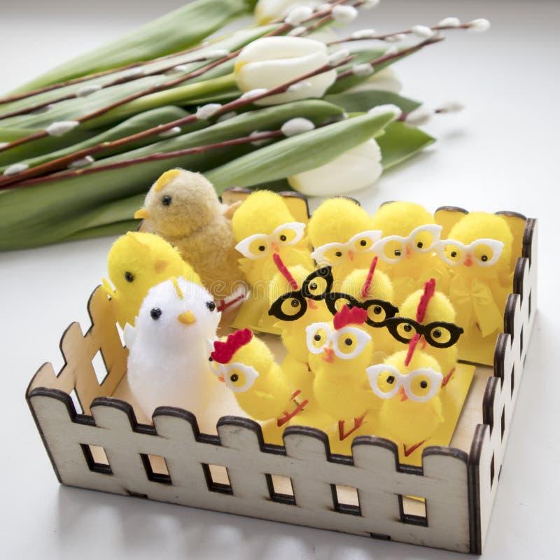A galinha amarela macia de pano com vidros em uma cesta de madeira como uma decoração de uma tabela para a Páscoa fotografia de stock royalty free