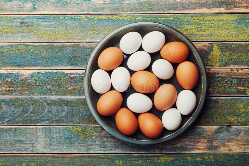 A galinha branca e marrom eggs na bacia do vintage na tabela de madeira rústica de cima de Alimento orgânico e da exploração agrí imagens de stock royalty free