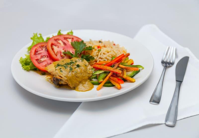 A galinha com arroz branco e os vegetais chapeiam a faca da forquilha fotografia de stock