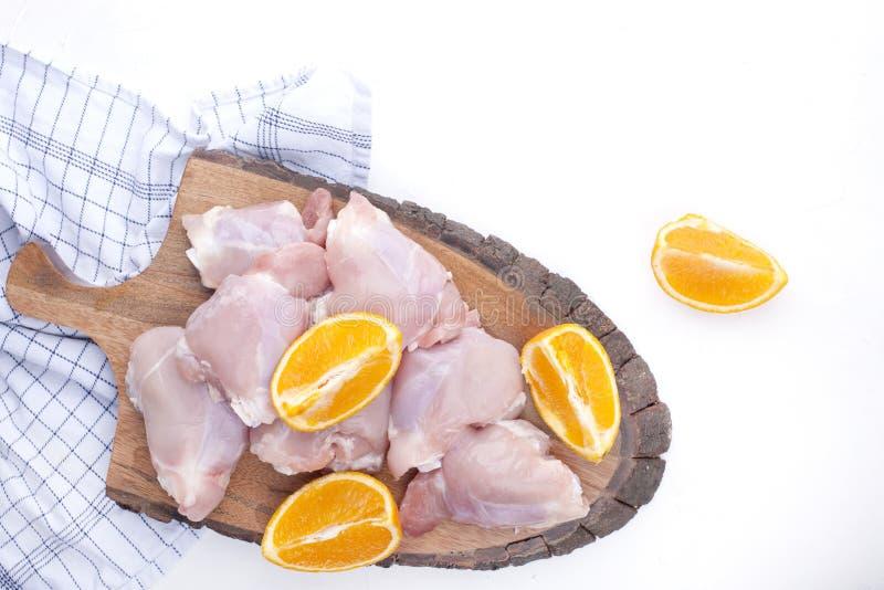 Galinha com as laranjas cruas em uma placa de madeira e em uma tabela branca Preparação de um jantar meaty delicioso Vista superi fotografia de stock