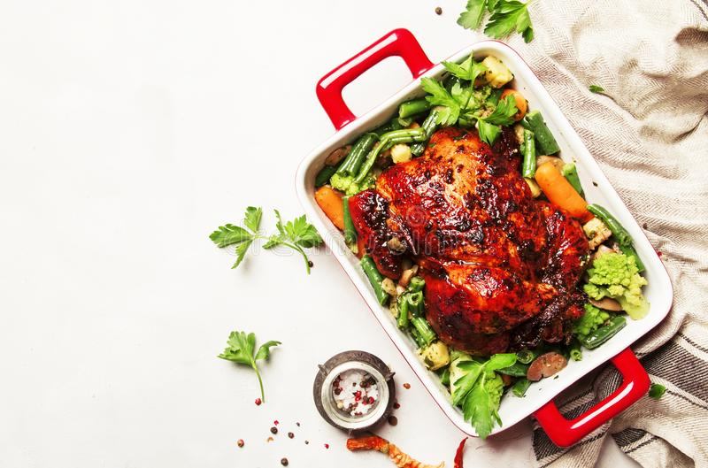 A galinha cozida no esmalte do mel com decora dos vegetais, b branco imagens de stock