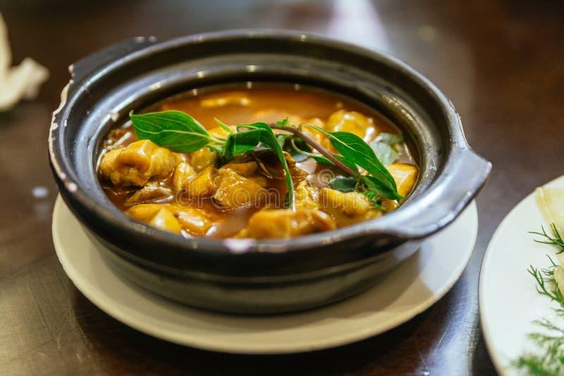 A galinha cozinhada estilo de Hanoi na cobertura do potenciômetro de argila com manjericão sae no restaurante em Hanoi vietnam imagem de stock