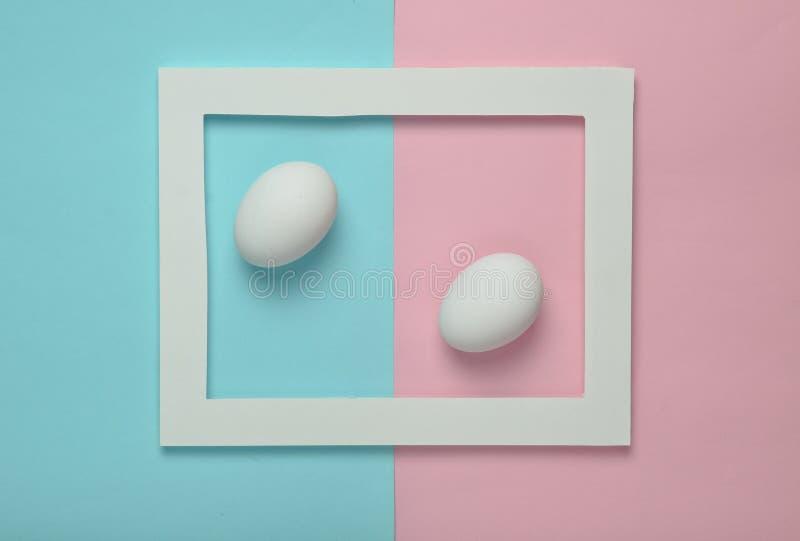 A galinha eggs em um quadro branco em um fundo pastel colorido Tendência minimalista fotografia de stock royalty free