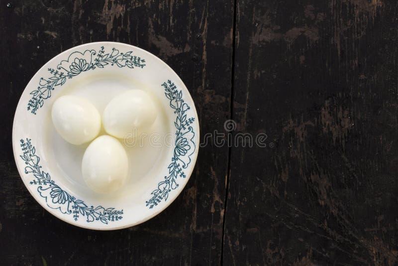 A galinha fervida eggs sem o shell em uns pires cerâmicos em um preto de madeira velho do fundo fotografia de stock