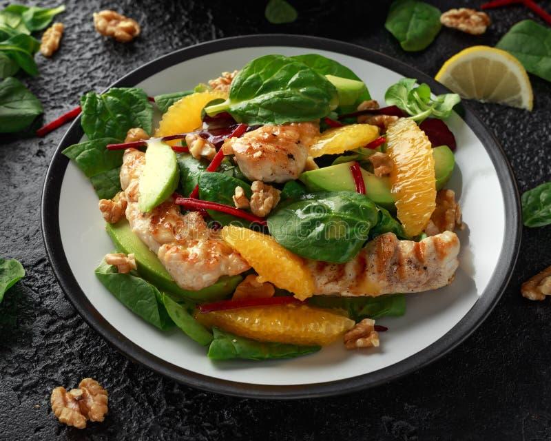 Galinha grelhada com salada da laranja e do abacate no fundo rústico foto de stock