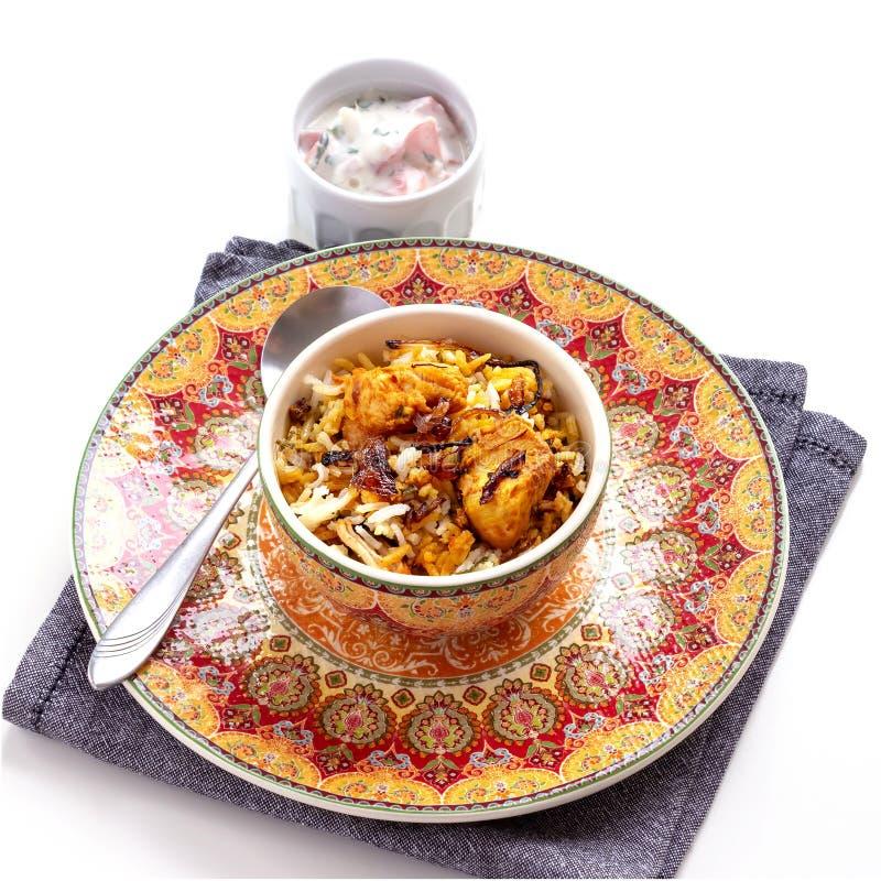 A galinha indiana Halal Biryani serviu com o raita do tomate do iogurte sobre o fundo branco Foco seletivo imagem de stock royalty free