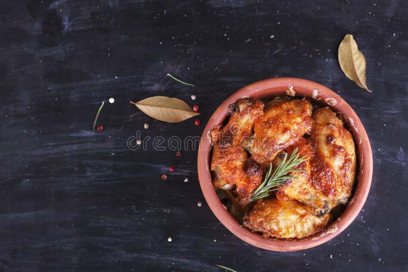 Galinha no molho de paprika cozido no forno na cerâmica Pés de galinha e wings imagem de stock