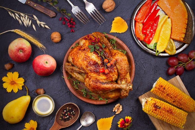Galinha ou peru inteiro, frutos e vegetais grelhados do outono: milho, abóbora, paprika Conceito do alimento do dia da ação de gr imagens de stock