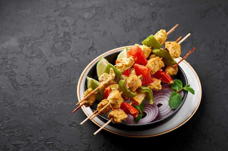 Galinha Tikka nos esquiadores em prato preto no fundo da ardósia escura Frango tikka é um prato de cozinha indiana Alimentos indi fotos de stock royalty free