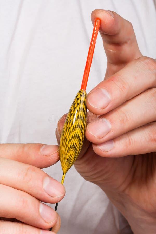 Galleggiante in mani del pescatore, primo piano immagine stock