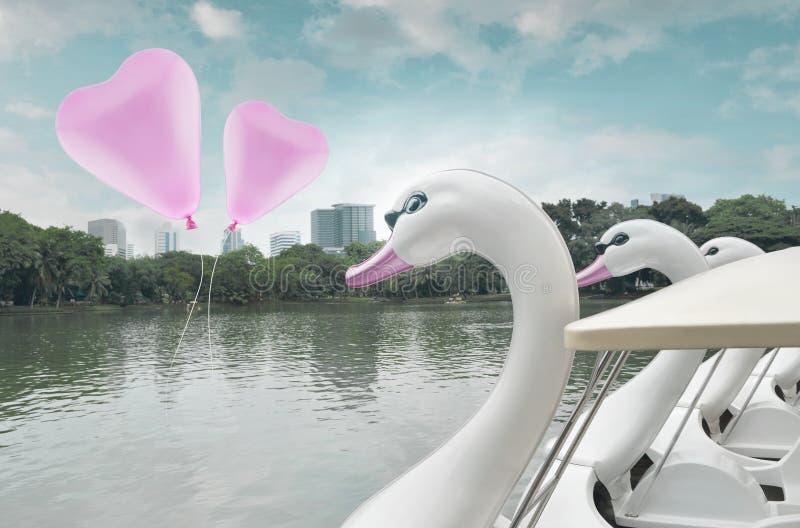 Galleggiante rosa del pallone di amore del cuore su aria con la barca del pedale del cigno al pub fotografia stock libera da diritti