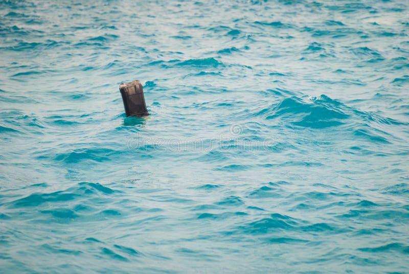 Galleggianti di plastica neri della scatola metallica nel mare Rifiuti domestici, concetto di mancanza di rispetto per l'ambiente fotografie stock