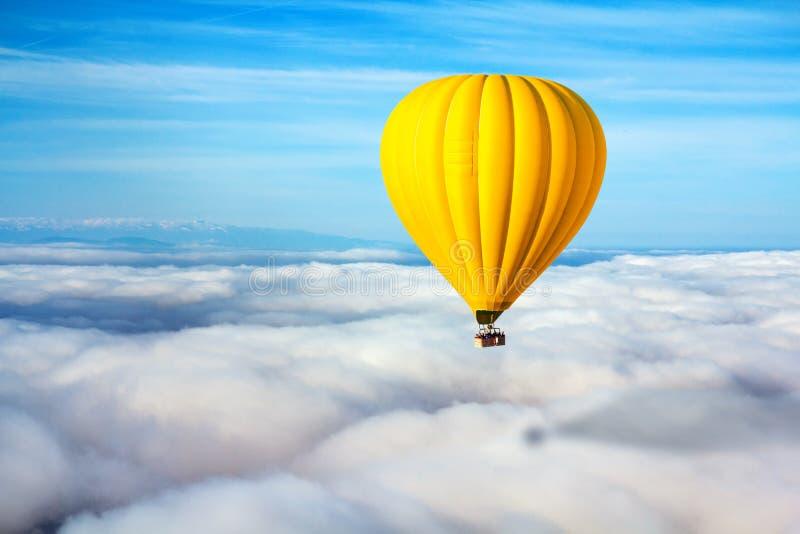 Galleggianti gialli soli di una mongolfiera sopra le nuvole Capo di concetto, successo, solitudine, vittoria fotografie stock libere da diritti