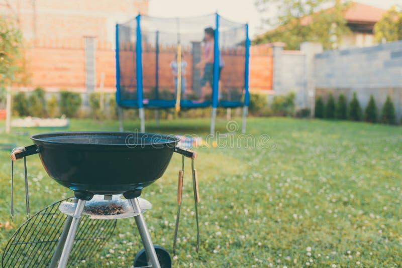 Galler för grillfest för kokkärlkolBBQ i trädgård eller trädgård Suddig utomhus- trampolin i bakgrunden Denna är mappen av format royaltyfri bild