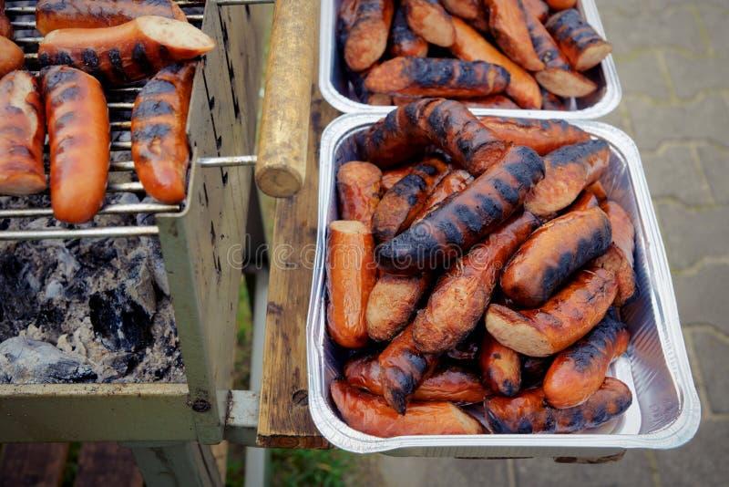 Galler grillad korv på picknicken som flammar gallret arkivbild
