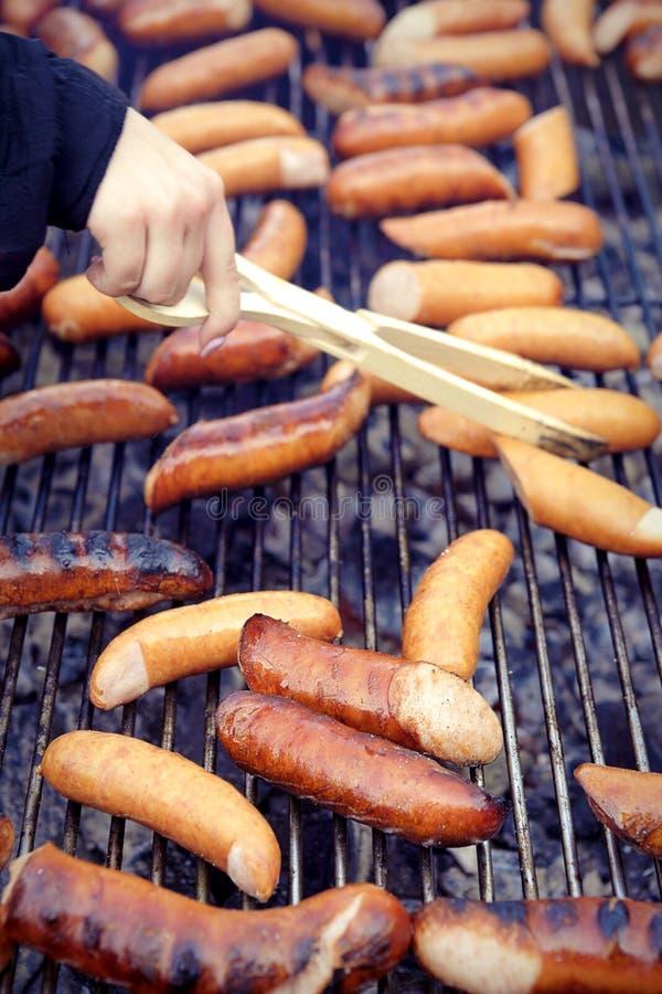 Galler grillad korv på picknicken som flammar gallret arkivfoto