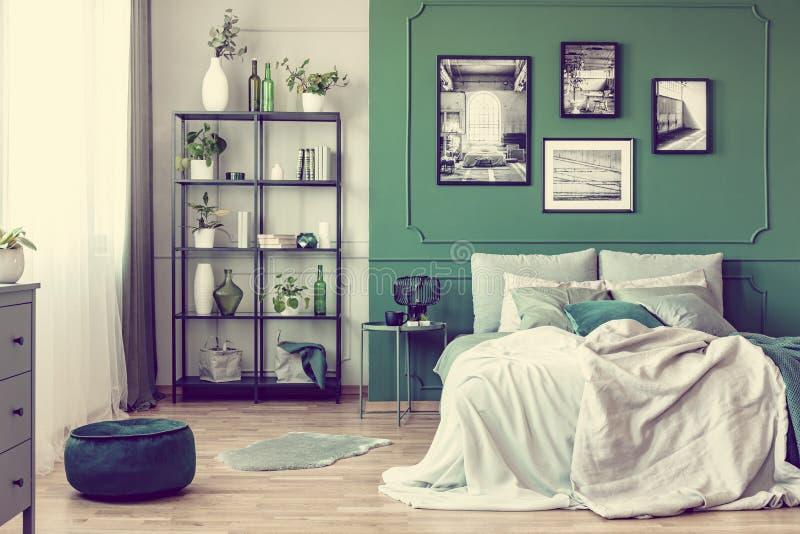 Galleri av den svartvita affischen på den gröna väggen bak konungformatsäng med kuddar och filten royaltyfria bilder