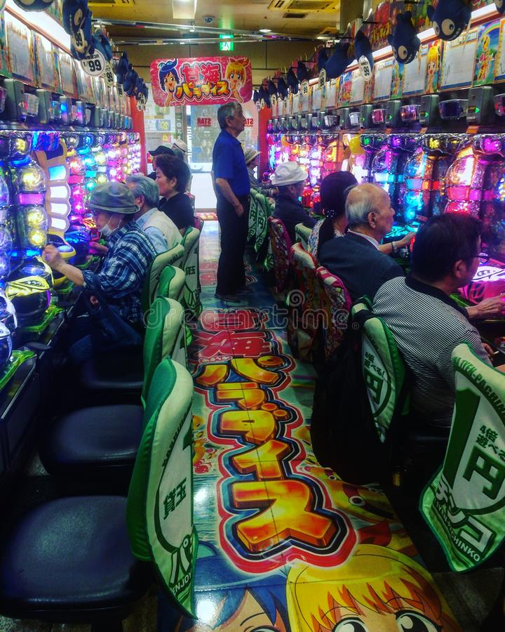 Galleria giapponese tipica di pachinko con la gente che gioca immagine stock libera da diritti