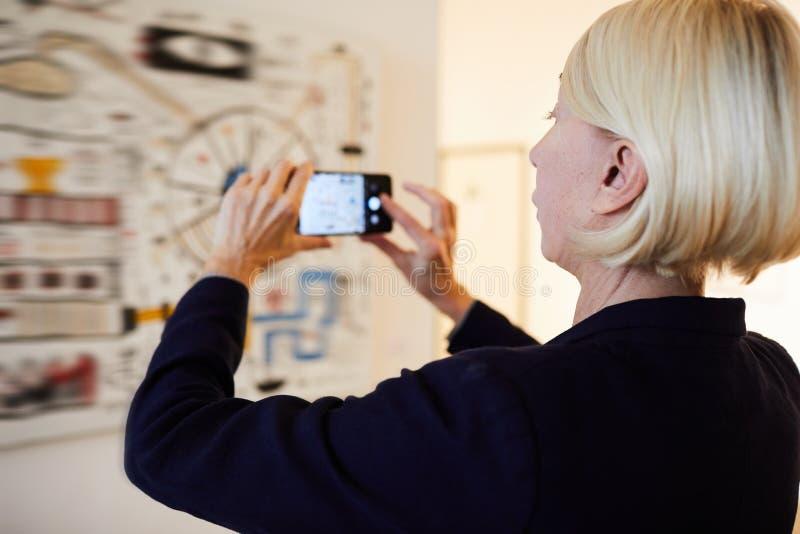 Galleribesökare som tar fotoet av målning royaltyfri foto