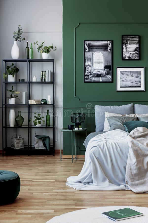 Gallery of black and white poster on green wall behind king size bed with pillows and blanket royalty free stock image