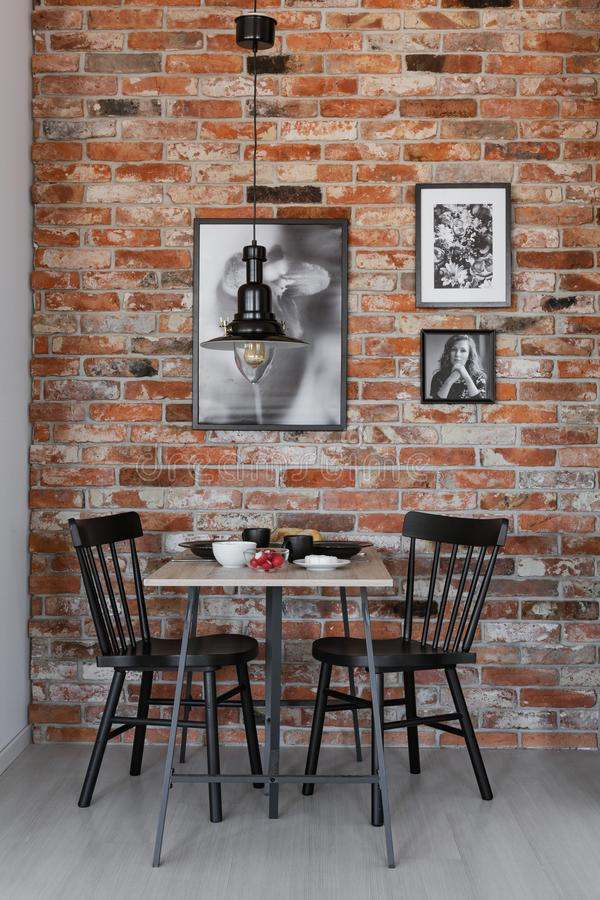 Gallery of black and white posters on brick wall of small dining room interior with table and black chair.  royalty free stock photography