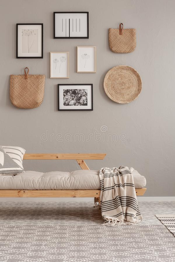 Gallery of posters in black frames and wicker kinck knack on beige wall of trendy living room interior with long settee with stock images