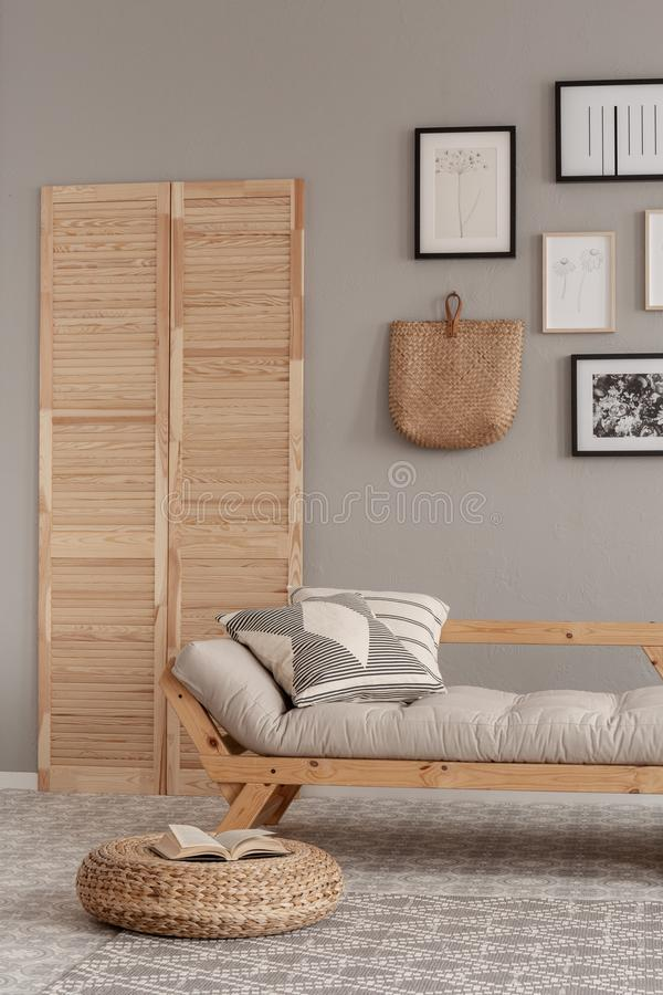 Gallery of posters in black frames and wicker kinck knack on beige wall of trendy living room interior with long settee with. Pillow royalty free stock image