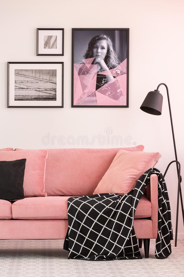 Posters on wall in fashionable living room interior with pink couch and industrial lamp. Gallery of posters on white wall in fashionable living room interior royalty free stock photos